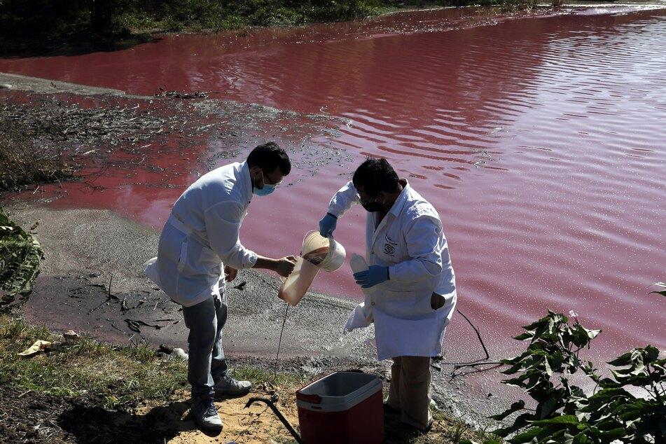 Marcelo Coronel (l.) und Francisco Ferreira, Techniker der Nationalen Universität, nehmen Wasserproben aus der rötlich gefärbten Lagune Cerro, an deren Ufer die Gerberei Waltrading sitzt.