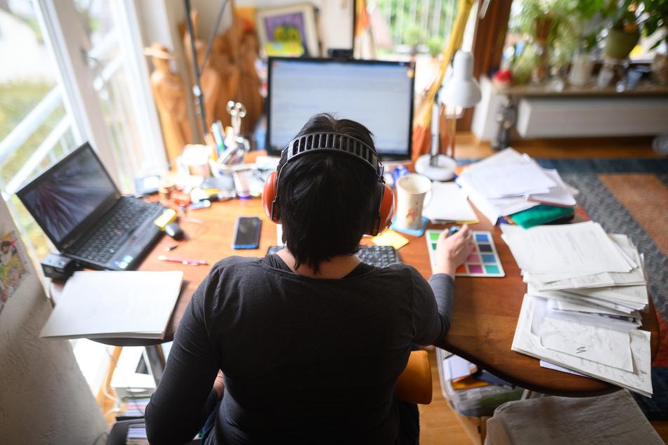 Eine Frau arbeitet mit Hörschutz im Homeoffice. (Symbolbild)