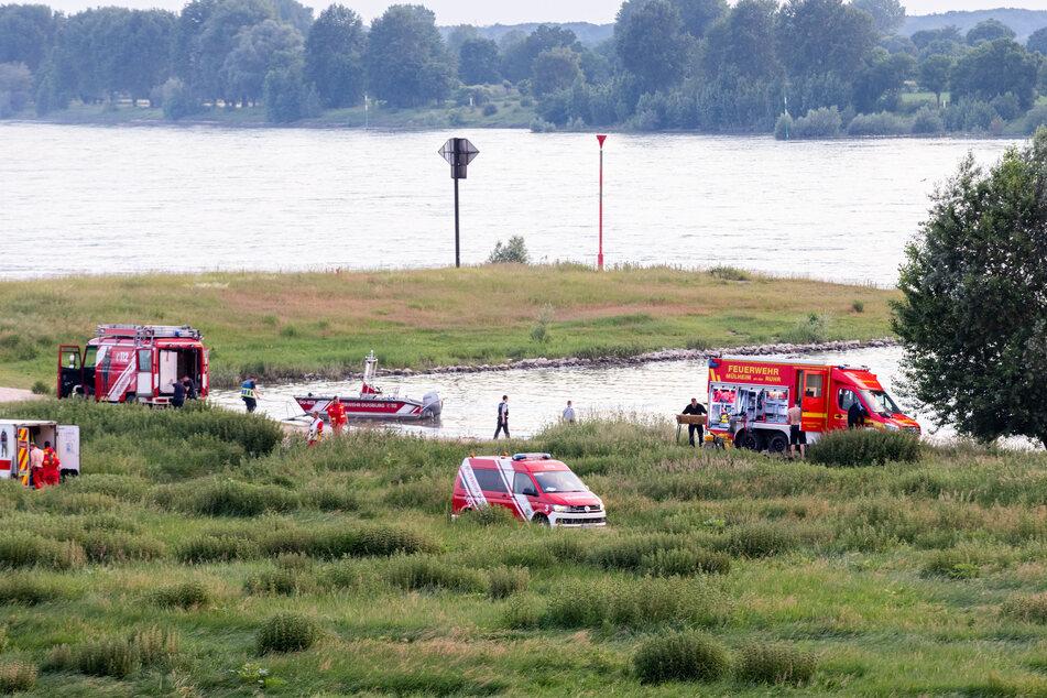 Einsatzkräfte der Polizei, Feuerwehr und DLRG am Ufer des Rheins.
