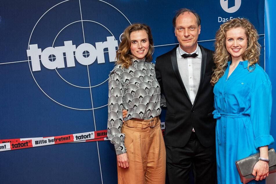 Die Schauspieler Karin Hanczewski (l-r), Martin Brambach und Cornelia Gröschel stehen vor Beginn des MDR-Tatortes vor einer Werbewand im Rundkino Dresden.