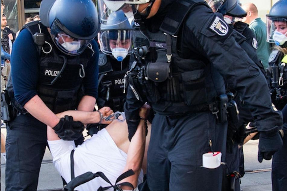 Polizisten führen bei einer Demonstration auf dem Berliner Alexanderplatz einen Mann ab.