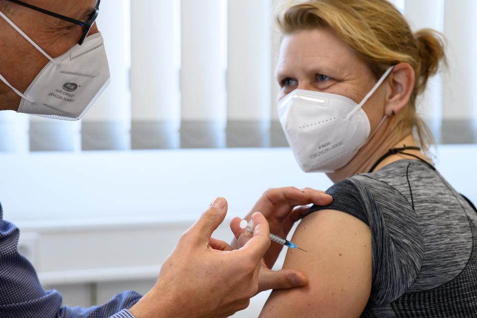 Ein Arzt verimpft einen Corona-Impfstoff.