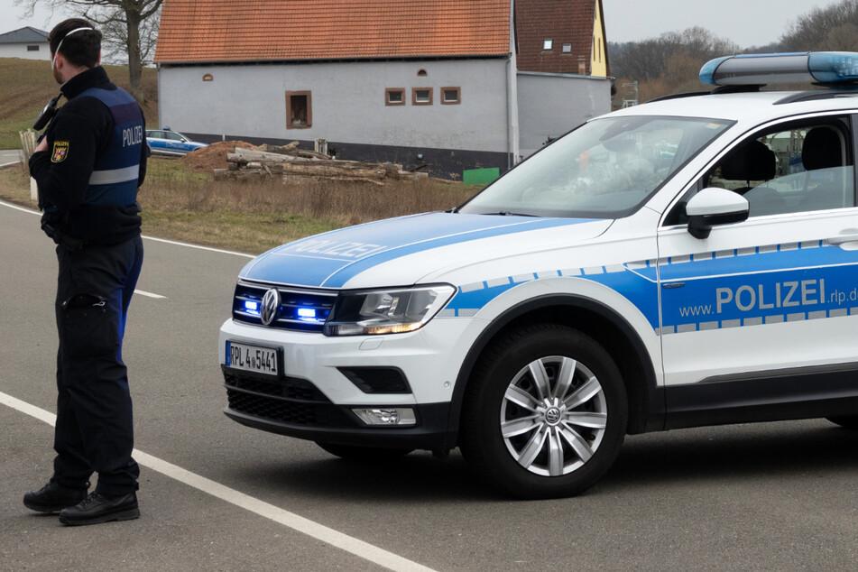 Ein Polizist sperrt mit einem Einsatzfahrzeug eine Straße in Weilerbach bei Kaiserslautern.