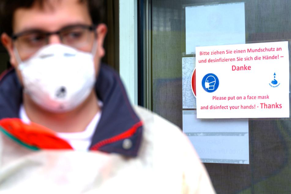 """Ein freiwilliger Mitarbeiter des Deutschen Roten Kreuzes (DRK) steht vor der Corona-Ambulanz des Klinikums Stuttgart im Katharinenhospital vor einem Schild, auf dem """"Bitte ziehen Sie sich einen Mundschutz an und desinfizieren Sie sich die Hände!"""" steht."""