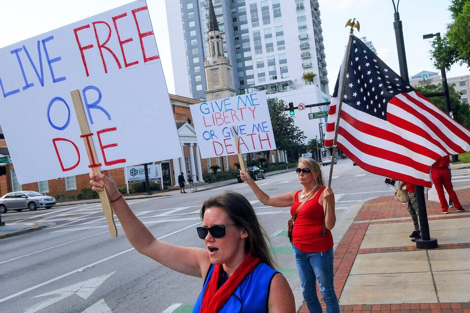 """Demonstranten halten Schilder mit den Aufschriften """"Live Free or Die"""" (Lebe frei oder strib) und """"Give me liberty or give me Death"""" (Gib mir Freiheit oder gib mir den Tod) bei einem Proteste gegen die Ausgangsbeschränkungen aufgrund des neuartigen Coronavirus. (Archivbild)"""