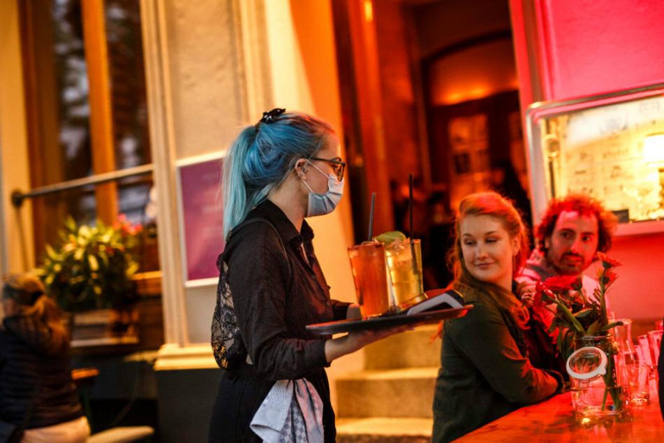 """Stephanie Llynch serviert Cocktails an einem Tisch vor der Cocktailbar """"Limonadier"""" im Stadtteil Kreuzberg."""
