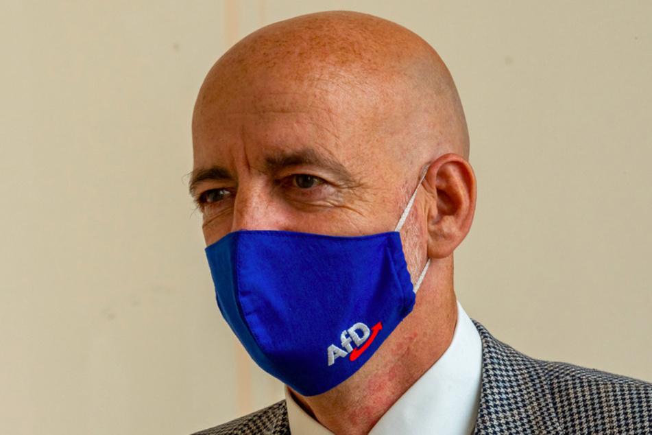 Martin Böhm, Abgeordneter der AfD, geht, vor Beginn der Plenarsitzung des bayerischen Landtags mit einer Mundschutzmaske mit AfD-Logo, durch die Gänge des Gebäudes.