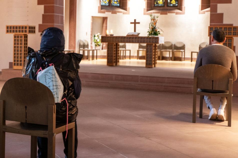 Weit voneinander entfernt sitzen Menschen im April in der Alten Nicolaikirche in Frankfurt und lauschen dem Spiel eines Organisten.