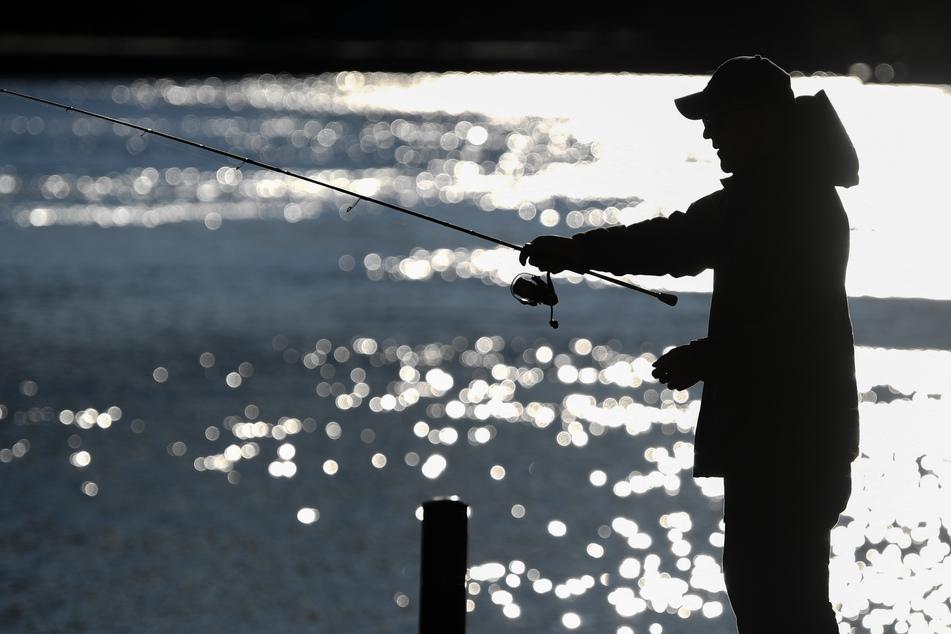 Ein Angler steht am späten Nachmittag am Ufer eines Flusses im Gegenlicht (Symbolbild).