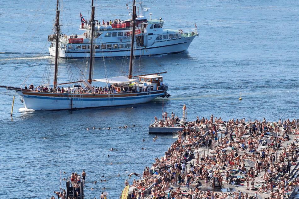 Norwegen, Oslo: Zwei Kreuzfahrtschiffe fahren vor dem vielbesuchten Badebereich Sorenga in der Nähe der Docks entlang.