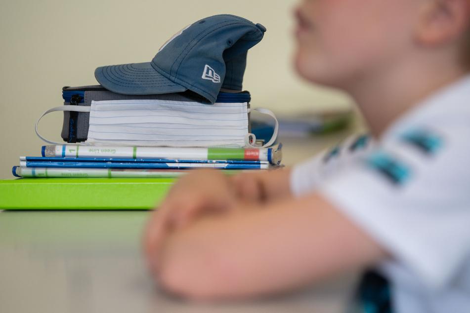 Eine Mund-Nasen-Bedeckung lehnt während einer Unterrichtsstunde einer fünften Klasse des Friedrich-Schiller Gymnasiums an Schulbüchern.