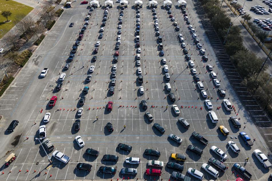 Autos stehen auf einem Parkplatz in Houston, USA in einer Schlange, während die Fahrer darauf warten, gegen das Coronavirus geimpft zu werden.