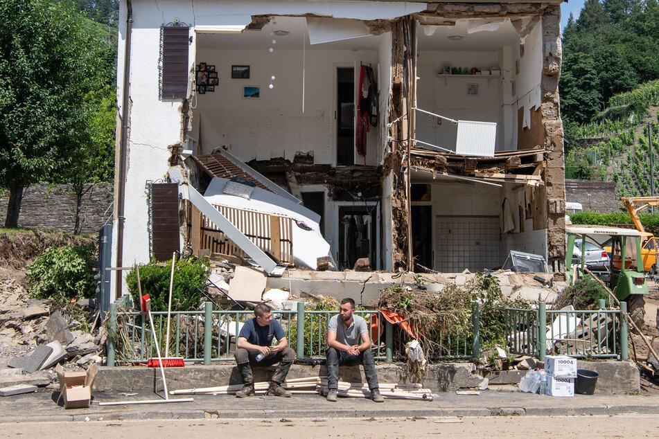 Marienthal, Rheinland-Pfalz: Zwei Männer sitzen vor einem Haus, dessen Fassade von der Flutwelle fortgerissen wurde.