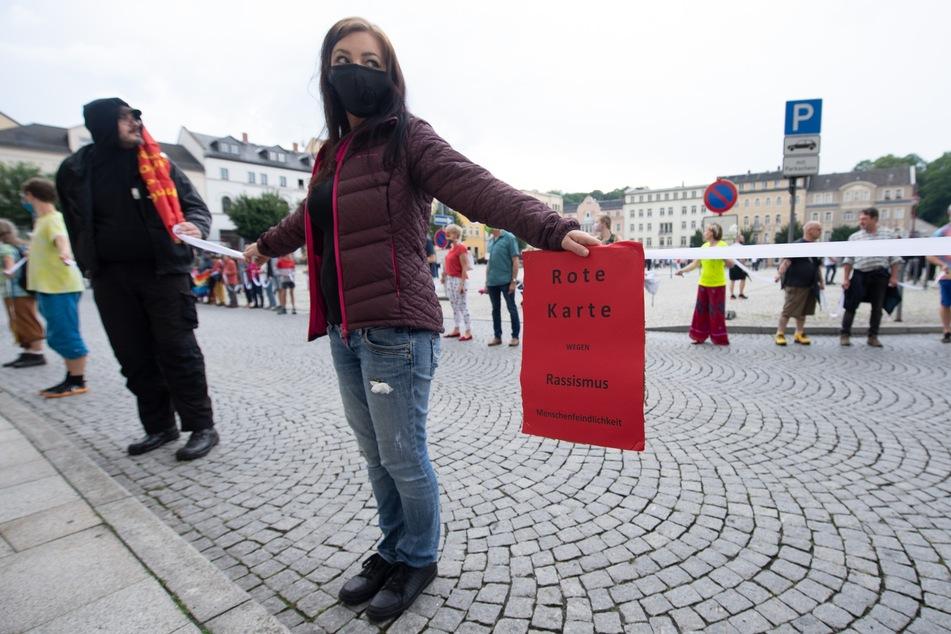 Teilnehmer einer Gegendemonstration in Form einer Menschenkette stehen während einer Kundgebung der AfD auf dem Marktplatz.
