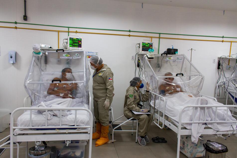 Krankenpfleger unterhalten sich mit Patienten auf der Intensivstation im Gilberto Novaes Municipal Field Hospital in Manaus.