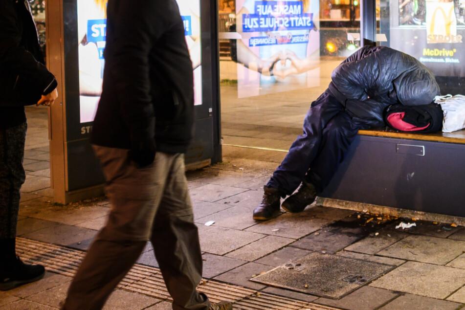 Ein Obdachloser kauert auf der Bank einer Bushaltestelle in Frankfurt am Main.