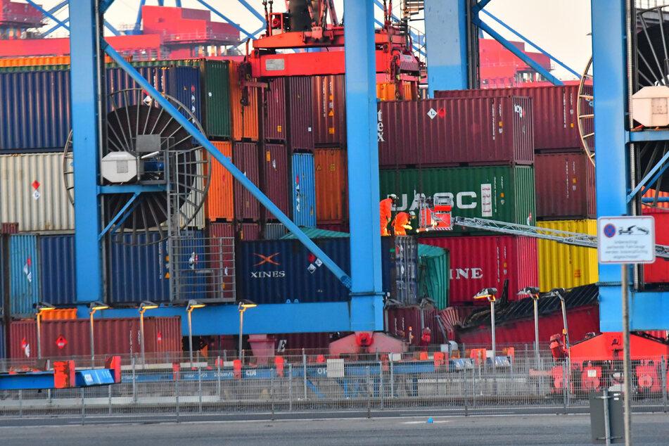 Feuerwehrleute in Schutzanzügen untersuchen die beschädigten Container im Hafen.