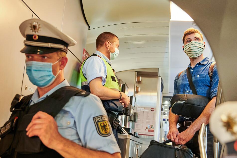 Beamte der Bundespolizei und Mitarbeiter der DB Sicherheit stehen in einem Zug und kontrollieren, ob die Corona-bedingte Maskenpflicht eingehalten wird.