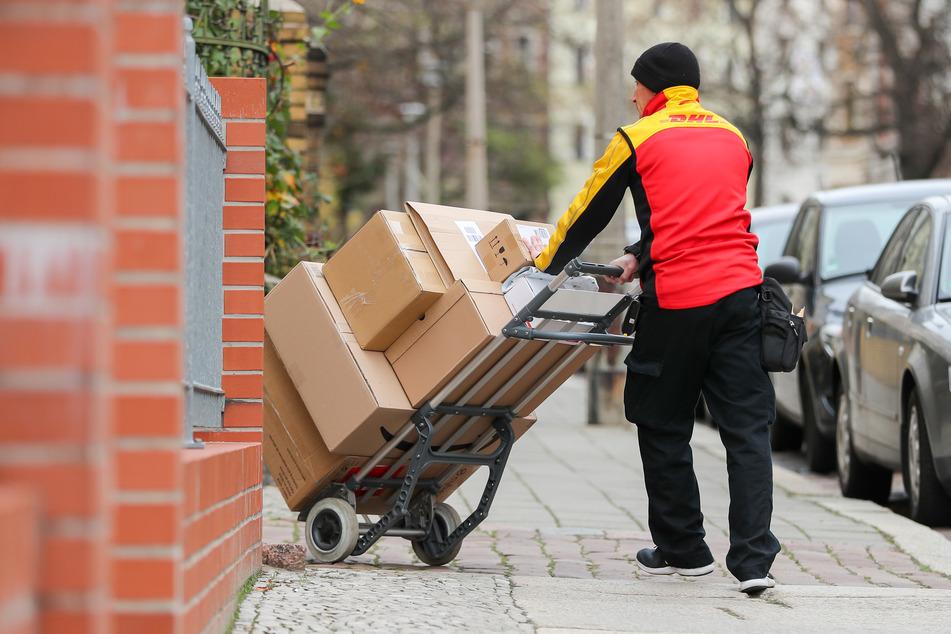 Ein DHL Paketzusteller geht mit einer Sackkarre voll Pakete zu einem Haus.