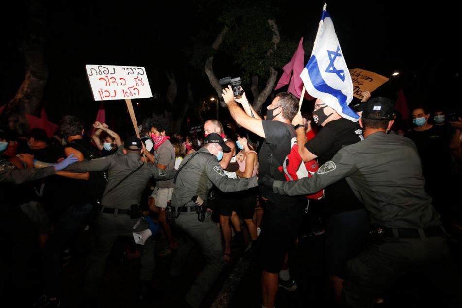 Polizisten stoßen in Tel Aviv mit Demonstranten zusammen, die trotz eines landesweiten Lockdowns aufgrund der Corona-Pandemie gegen den Premierminister Netanjahu protestieren.