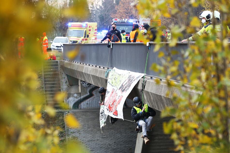 Zwei Aktivisten hängen neben ihrem Banner über der A4-Fahrbahn.