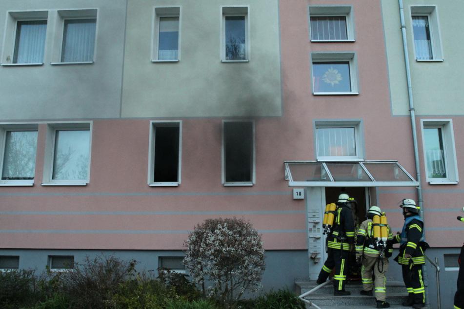 Rauch dringt aus einem Fenster der brennenden Wohnung, während die Feuerwehr das Wohnhaus betritt.