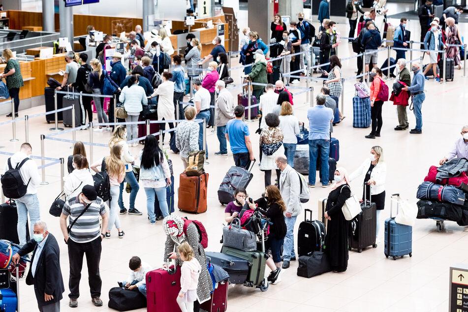 Flugpassagiere mit Mund-Nasen-Schutzmasken stehen an Check-In Schaltern des Flughafens Hamburg.
