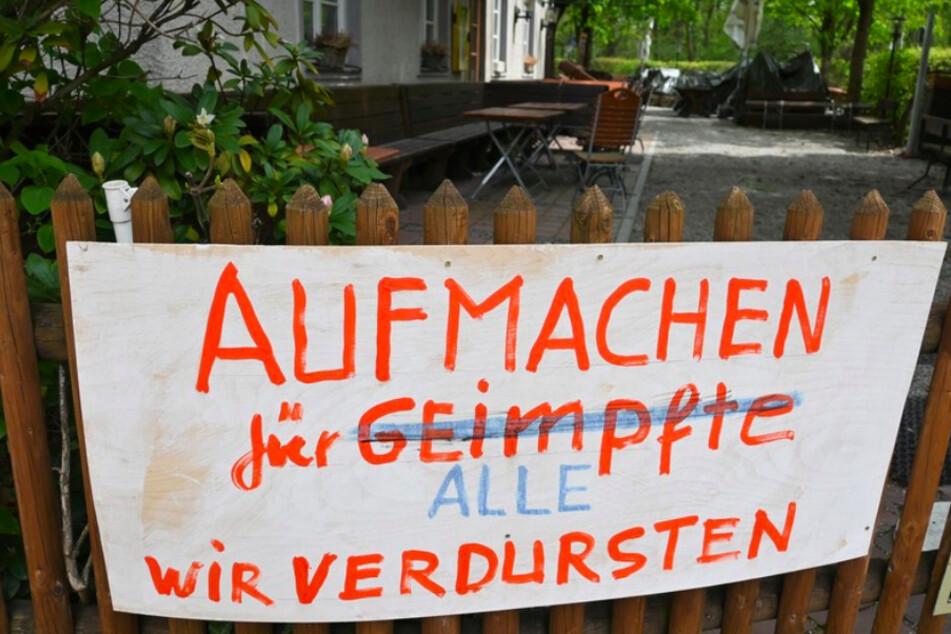 Ein Banner mit der Forderung, die Biergärten wieder zu öffnen, hängt am Zaun eines Biergartens in München.
