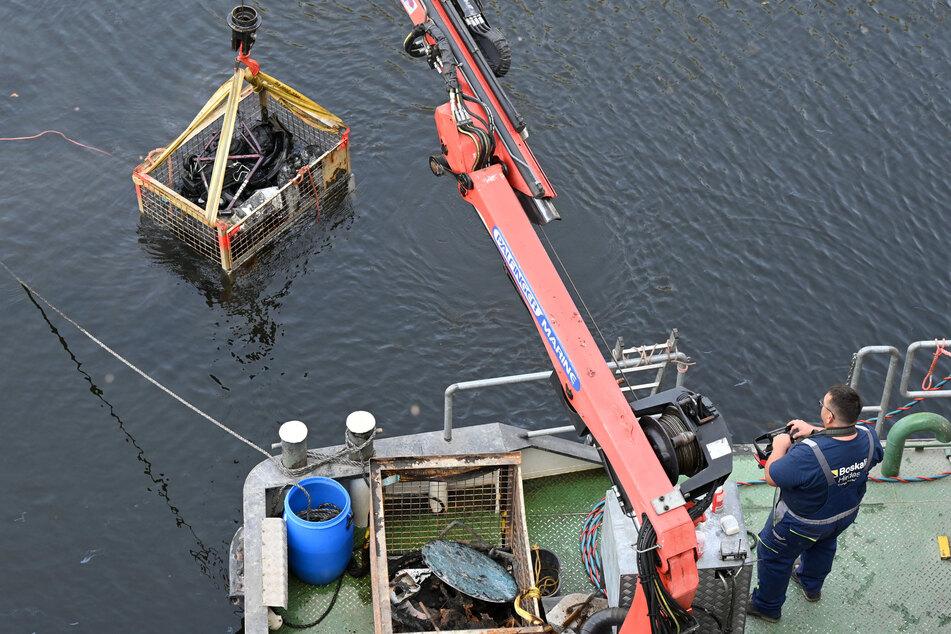 Mit einem Kran werden immer wieder mit Schrott gefüllte Eisenboxen aus dem Kanal geholt. Ein Ende ist nicht absehbar.