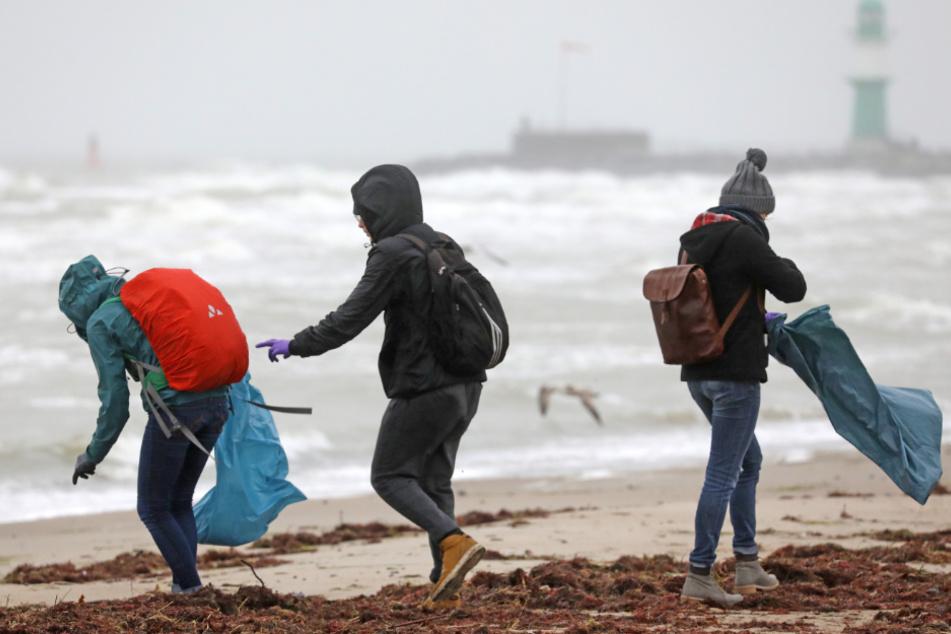 Freiwillige sammeln Müll am Ostseestrand von Warnemünde. (Archivbild)