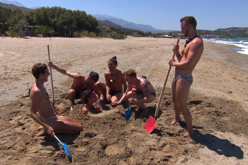 Beim Gruppendate wird Gino am griechischen Kreta-Strand eingebuddelt.