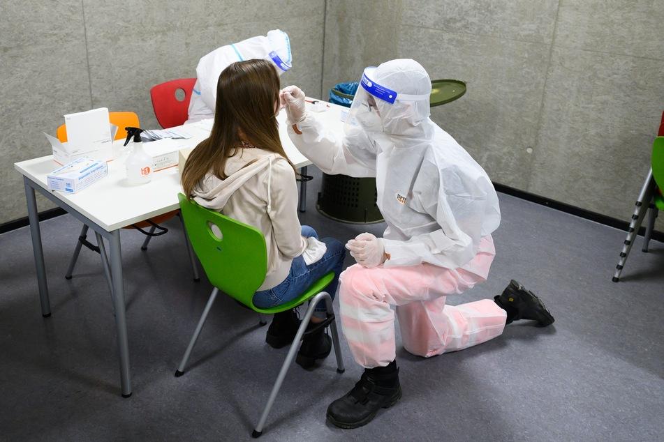 Eine Schülerin sitzen während eines freiwilligen Corona-Schnelltests in der Mensa des Schulcampus Gehestraße vor Mitarbeitern des Deutschen Roten Kreuz (DRK) in Dresden.