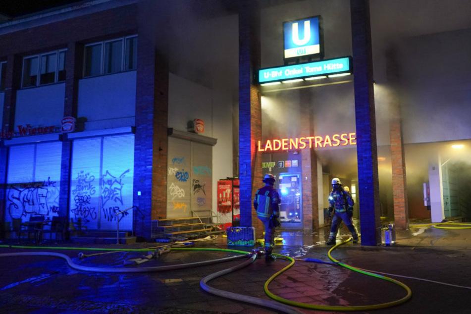 Einsatzkräfte der Feuerwehr löschen einen Brand in der Ladenzeile des U-Bahnhofs Onkel Toms Hütte.