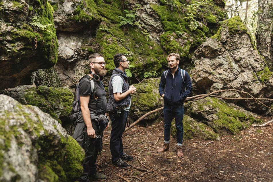 """Beim Streifzug durch das Zittauer Gebirge: Felix Räuber (36, r.) und zwei Musiker von """"Forest Roots"""" an der Karasek-Höhle."""