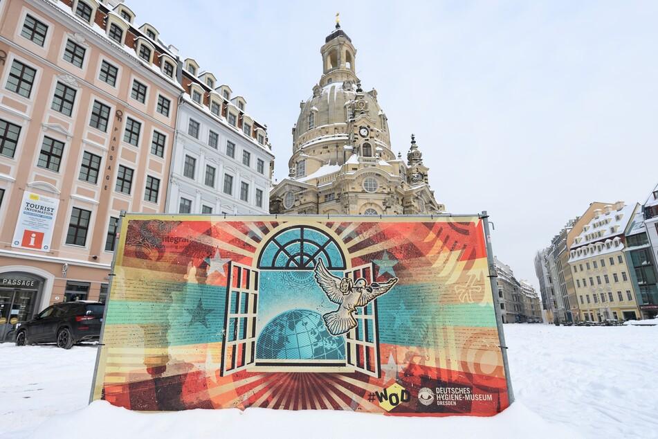 Ein Kunstprojekt der Initiative Weltoffenes Dresden #WOD mit einem Motiv des Streetartkünstler Lars P. Krause steht auf dem Neumarkt vor der Frauenkirche im Schnee.