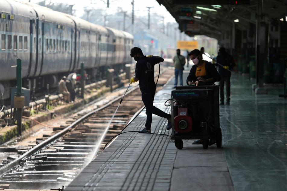 Indien, Jammu: Ein Arbeiter desinfiziert die Bahngleise als Vorsichtsmaßnahme gegen das Coronavirus.