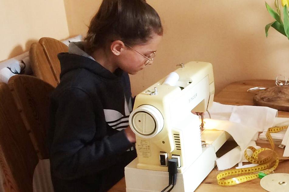 Hanna, die Tochter von Damen-Gewandmeisterin Isabel Kulitzscher, sitz tnach den Schulaufgaben an der Nähmaschine.