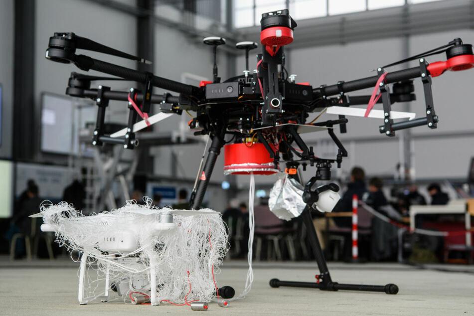 """Eine von einer Jagddrohne des Typs """"AirRobot AR200"""" (r.) gefangene Drohne steht im Fangnetz bei einer Präsentation. (Archivbild)"""