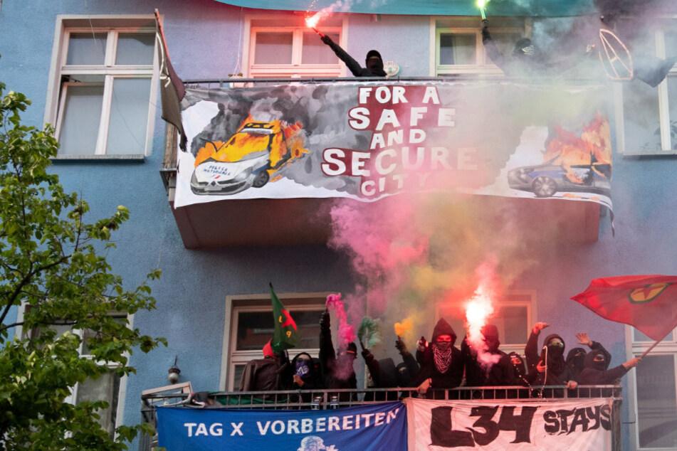"""Unterstützer der linksradikalen """"Revolutionären 1. Mai-Demonstration"""" stehen mit Pyrotechnik in der Hand auf Balkonen in Friedrichshain. (Archivbild)"""