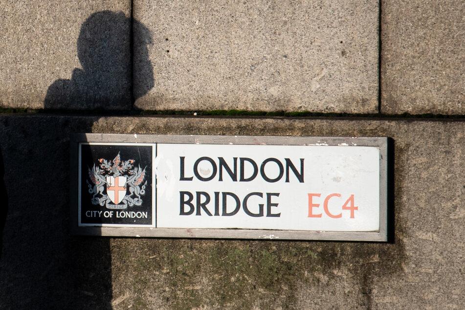 Der Schatten eines Mannes mit einer schützenden Gesichtsmaske ist auf einem Schild auf der London Bridge zu sehen, als Pendler die London Bridge im Zentrum Londons während des morgendlichen Berufsverkehrs überqueren.