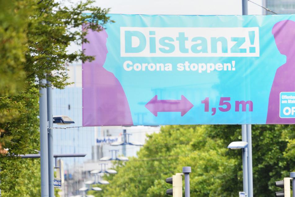 """Ein Plakat mit der Aufschrift """"Distanz! Corona stoppen!"""" prangt am Ortseingang – die Offenbacher Bürger müssen strengere Corona-Regeln beachten."""