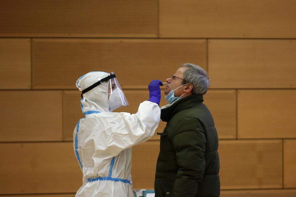 Ein medizinischer Mitarbeiter in Schutzkleidung führt einen Corona-Test an einem Mann durch.
