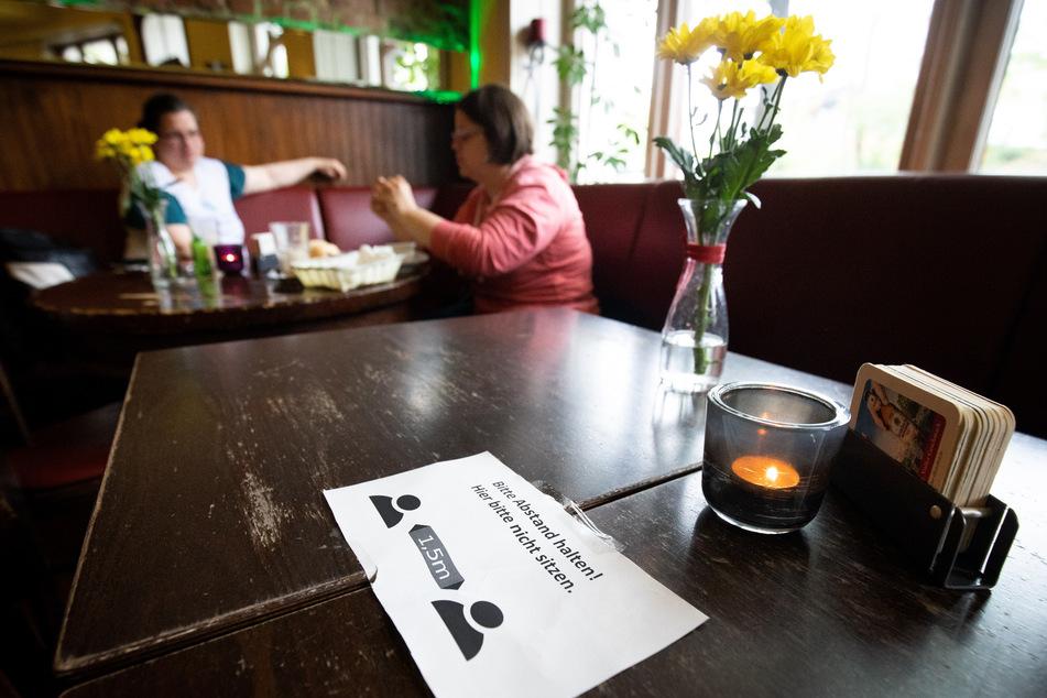 """Ein Zettel mit der Aufschrift """"Bitte Abstand halten!"""" liegt in einem Hamburger Lokal."""