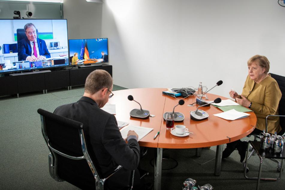 Bundeskanzlerin Angela Merkel (66, CDU) und der Regierende Bürgermeister von Berlin, Michael Müller (55, SPD), zu Beginn der Videokonferenz mit den Ministerpräsidentinnen und Ministerpräsidenten der Länder sowie Mitgliedern der Bundesregierung über den Kurs im Kampf gegen die Corona-Pandemie bis zum Jahresende. Auf dem Videoschirm im Hintergrund ist Nordrhein-Westfalens Ministerpräsident Armin Laschet (59, CDU) zu sehen.
