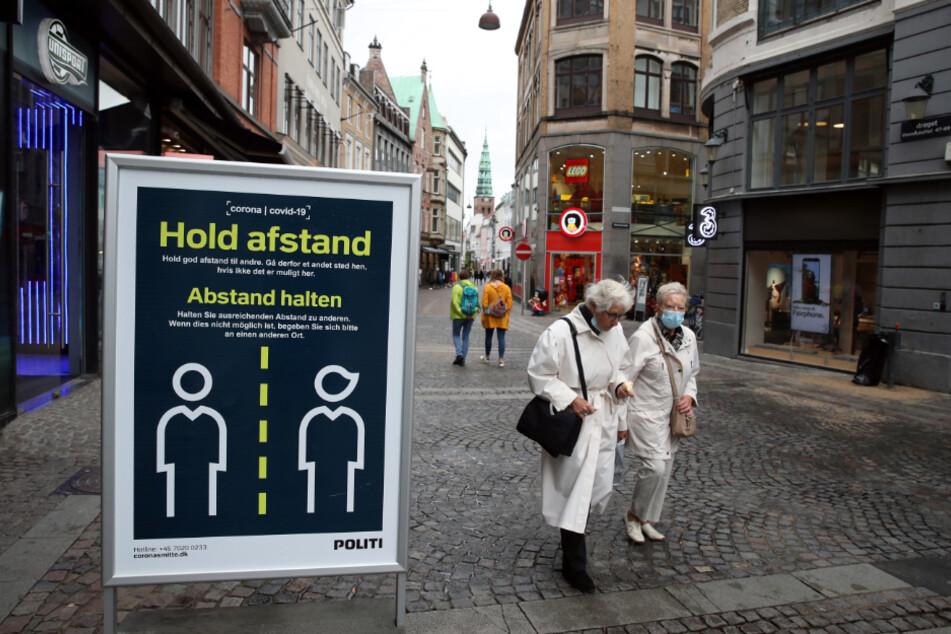 """Dänemark, Kopenhagen: """"Abstand halten"""" steht auf einem Schild in einer Straße in Kopenhagen."""
