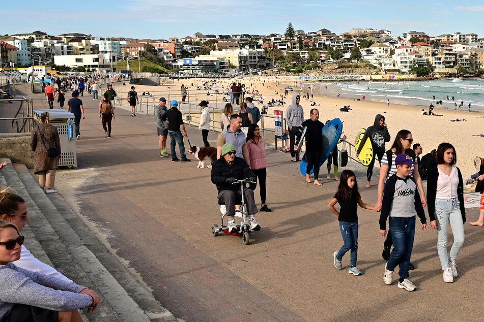 Menschen gehen an der Promenade des Bondi Beach spazieren.