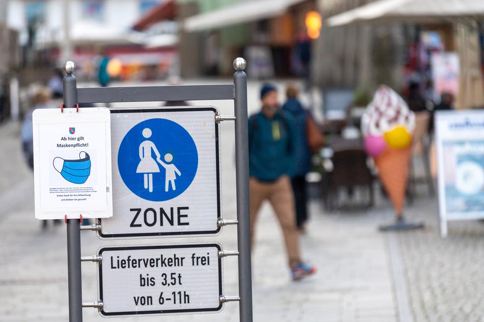 """Ein Schild mit der Aufschrift """"Ab hier gilt Maskenpflicht!"""" hängt am Eingang der Berchtesgadener Fußgängerzone."""