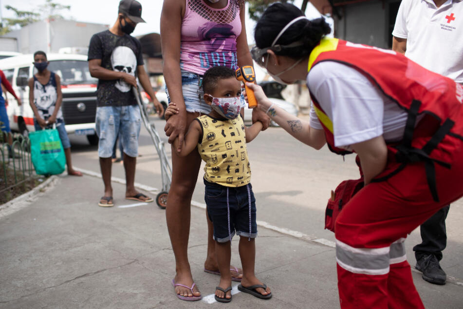 Rio De Janeiro: Ein Mitglied des Roten Kreuzes überprüft die Temperatur eines Kindes auf einem Großmarkt während der Corona-Pandemie. Brasilien hat 1.106.470 Covid-19-Infizierte bestätigt.