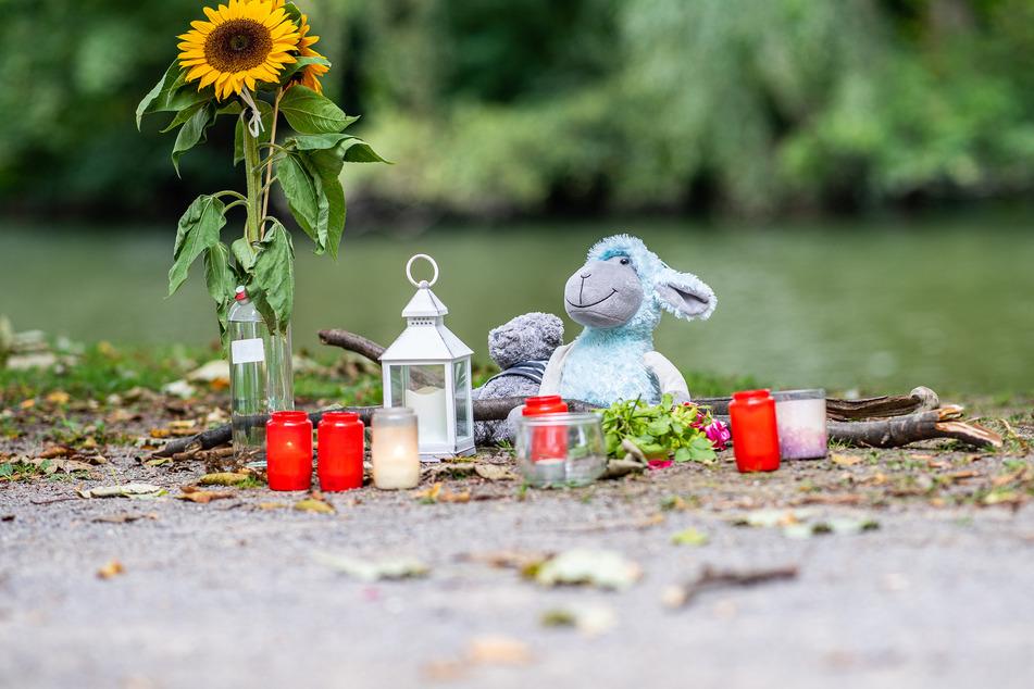 Zwei Stofftiere, Kerzen und Sonnenblumen stehen an dem kleinen See am Oberlandesgericht in Hamm, wo am Sonntag die Leiche der 25-Jährigen gefunden wurde.