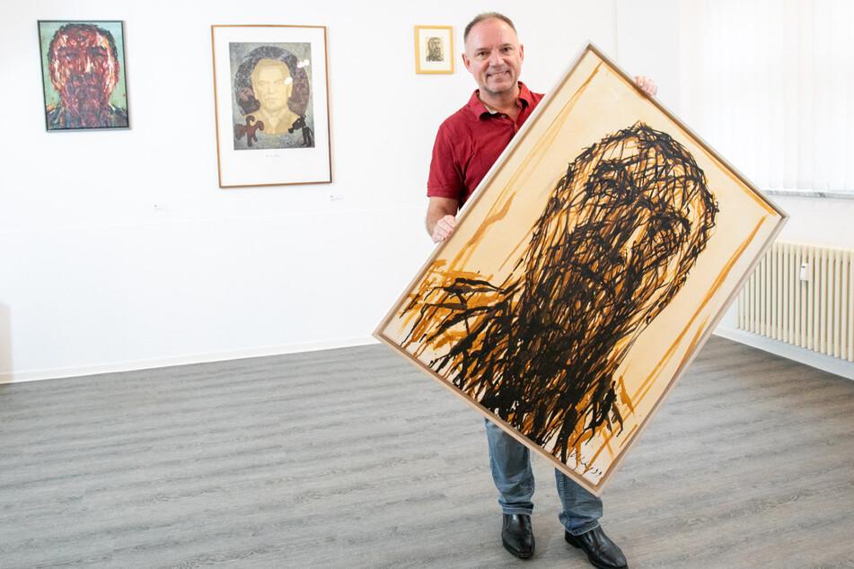 Galerist André Döhring (54) mit lauter Gerhard Schröders. In seinen Händen ein Original von Max Uhlig (83).
